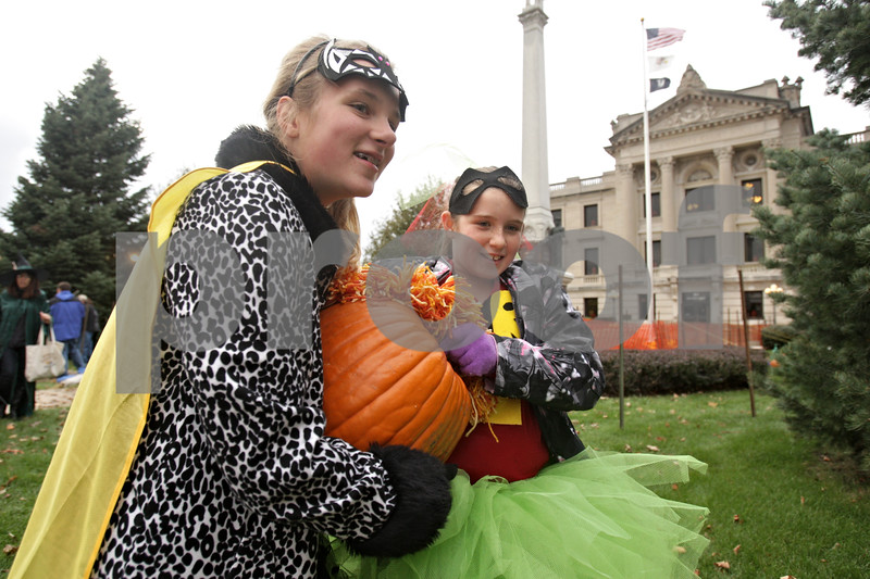 Rob Winner – rwinner@shawmedia.com<br /> <br /> Caroline Menzer (left), 10, and Jaedyn Slutz, 10, both of Sycamore, carry Slutz's pumpkin entry to a designated spot on the DeKalb County Courthouse lawn at the Sycamore Pumpkin Festival in Sycamore, Ill., Wednesday, Oct. 23, 2013.