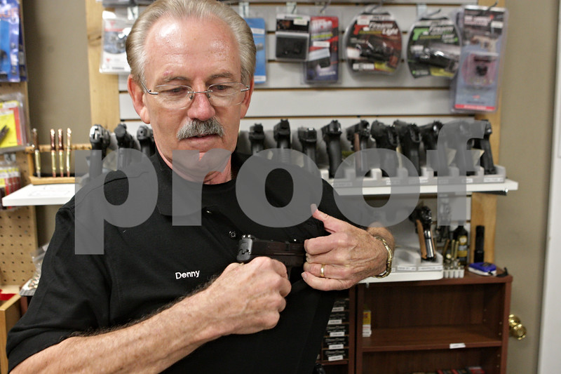 Rob Winner – rwinner@shawmedia.com<br /> <br /> Dennis Leifheit, owner of ZZ Cop's Gun Room in Sycamore, Ill., demonstrates how to conceal a firearm using a 5.11 concealed carry shirt at his business on Friday, Oct. 18, 2013.