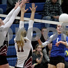 Monica Maschak - mmaschak@shawmedia.com<br /> Bridget Halat sends the ball into a pair of blockers in the second set against Richmond-Burton on Tuesday, October 22, 2013. The Cogs lost the match.