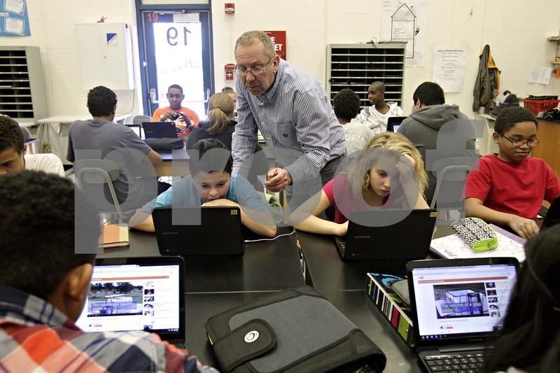 Rob Winner – rwinner@shawmedia.com<br /> <br /> Roger Christensen, an instructor at Clinton Rosette Middle School in DeKalb, helps Edgar Hernandez (left), 13, as Hernandez works on a science lab using a laptop on Monday, Oct. 21, 2013.