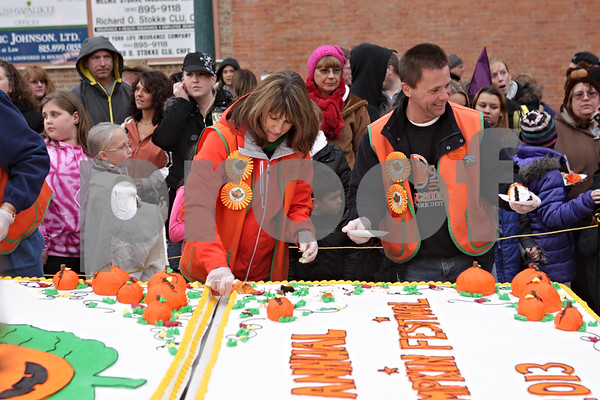 Rob Winner – rwinner@shawmedia.com<br /> <br /> Marianne Vogel (left) and Bart Desch help cut and serve cake during the opening ceremony at the Sycamore Pumpkin Festival on Wednesday, Oct. 23, 2013.