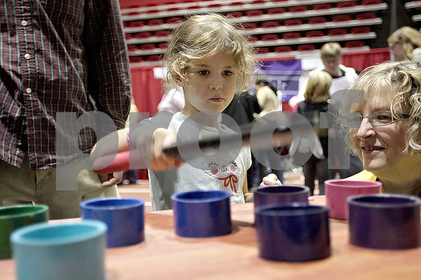 Monica Maschak - mmaschak@shawmedia.com<br /> Maeve Koch, 5, plays the PVC organ to demonstrate different tones from different lengths of PVC pipes at this year's Annual Celebration of Science, Technology, Engineering and Math (STEM) at  the Northern Illinois University Convocation Center on Saturday, October 19, 2013.