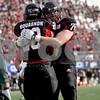 Monica Maschak - mmaschak@shawmedia.com<br /> Offensive lineman Ryan Brown hugs running back Joel Bouagnon after scoring a touch down in the first quarter against Eastern Michigan University on Saturday, October 26, 2013. The Huskies won 59-20.
