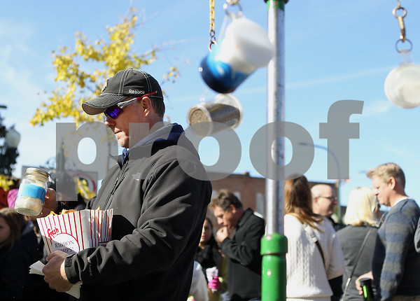 Erik Anderson - For the Daily Chronicle<br /> Tom Kirkham of Rockford pours cheese on his ribbon chips during the Sycamore Pumpkin Festival in downtown Sycamore on Sunday, October 27, 2013.