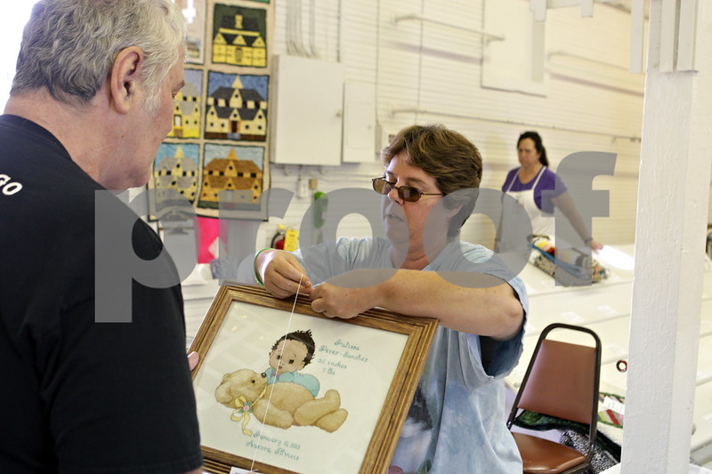 Rob Winner – rwinner@shawmedia.com<br /> <br /> Sue Smith (center) of DeKalb tags her cross-stitch entry with the help of her husband, Tom Smith, inside the Home Arts Building on Monday, Sept. 2, 2013 at the Sandwich Fairgrounds.