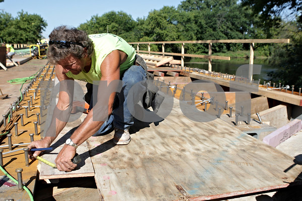 Rob Winner – rwinner@shawmedia.com<br /> <br /> Jim Coulter makes a measurement while working on the construction of the bridge over the Kishwaukee River on Baseline Road just south of Genoa, Ill., Friday, Aug. 23, 2013.