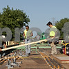 Rob Winner – rwinner@shawmedia.com<br /> <br /> Workers including Fred Kastning (from left to right), Shannon Pierce and Karolyn Thorne rebuild the bridge over the Kishwaukee River on Baseline Road just south of Genoa, Ill., Friday, Aug. 23, 2013.