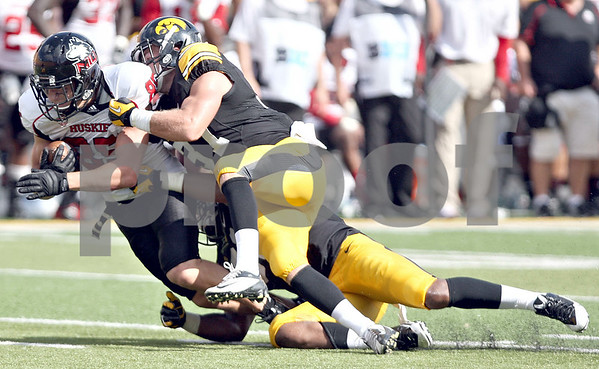 Monica Maschak - mmaschak@shawmedia.com<br /> Wide Receiver Angelo Sebastiano gets taken down by two Hawkeyes during the second quarter against Iowa at Kinnick Stadium on Saturday, August 31, 2013. The Huskies won the game 30-27.