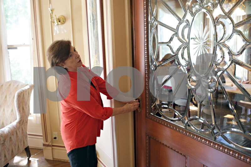 Rob Winner – rwinner@shawmedia.com<br /> <br /> Catherine Houis closes a pocket door decorated with beveled crystal lead glass leading to the dining room at her home located at 329 N. Third Street in DeKalb. The house which is for sale was built in 1884.