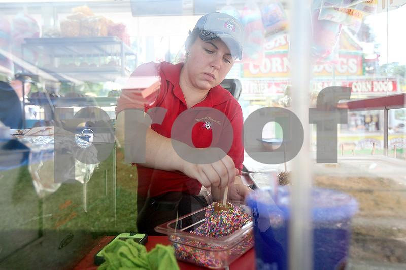 Monica Maschak - mmaschak@shawmedia.com<br /> Chanel Payne, with Parnel Foods Inc., rolls a carmel apple in sprinkles at the Sandwich Fair on Saturday, September 7, 2013.