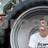 Monica Maschak - mmaschak@shawmedia.com<br /> Sycamore senior and linebacker Logan Schneider sits in the tire of an Old Elm Farms tractor while talking to his teammates at the Made in Sycamore event on Tuesday, September 10, 2013. Community members got to see first-hand what is made in Sycamore.