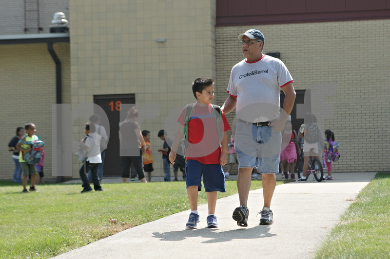 Rob Winner – rwinner@shawmedia.com<br /> <br /> Founders Elementary School student Yair de la Cruz, 7, leaves school after an early dismissal on Monday in DeKalb with his grandfather Jose Flores.<br /> <br /> Monday, Sept. 9, 2013