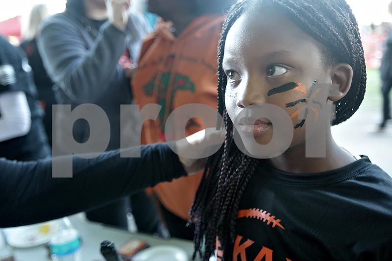 Monica Maschak - mmaschak@shawmedia.com<br /> Ania Stump gets her face painted black and orange for DeKalb spirit before the game against Sycamore at Huskie Stadium on Friday, September 13, 2013.