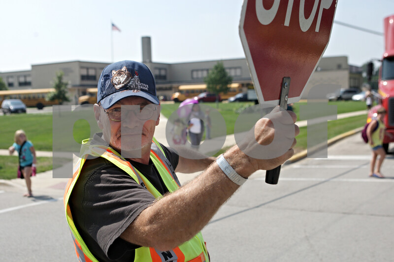 Rob Winner – rwinner@shawmedia.com<br /> <br /> Coy Richards ensures the safety of students and their parents crossing East Taylor and South Seventh streets outside Founders Elementary School in DeKalb after an early dismissal on Monday afternoon due to the heat.<br /> <br /> Monday, Sept. 9, 2013