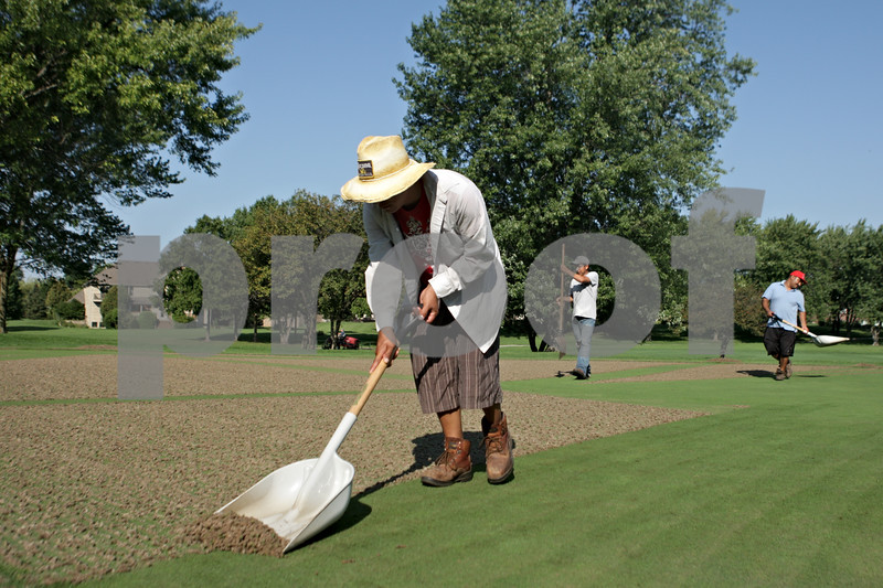 Rob Winner – rwinner@shawmedia.com<br /> <br /> Workers including Marco Miranda (front) use a shovel to clear compacted soil from the green on the 13th hole at the Kishwaukee Country Club in DeKalb after the hole was aerated on Tuesday, Sept. 10, 2013.