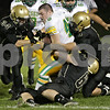 Rob Winner – rwinner@shawmedia.com<br /> <br /> Sycamore defenders Jack Dargis (34), Brett Weaver (4) and Brandon Nelson (65) combine for a tackle of Geneseo running back Brandon Mizlo (46) in the first quarter of their game in Sycamore, Ill., Friday, Sept. 20, 2013.