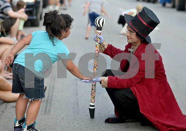 Monica Maschak - mmaschak@shawmedia.com<br /> Social Studies teacher Michael Petrov, dresses as Willie Wonka, hands candy to a girl at DeKalb's homecoming parade on Thursday, September 19, 2013. Petrov was representing the Outdoor Adventure Club.