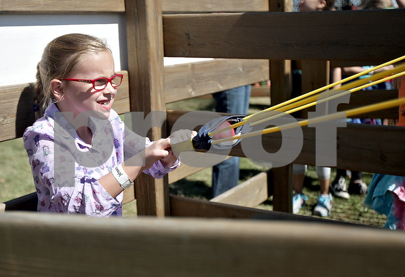 Monica Maschak - mmaschak@shawmedia.com<br /> Laura Vesely, 7, of Woodridge, pulls back on an apple launcher before letting go at Jonamac Orchards on Saturday, September 14, 2013. The Orchards offer barnyard activities and apple picking through October.