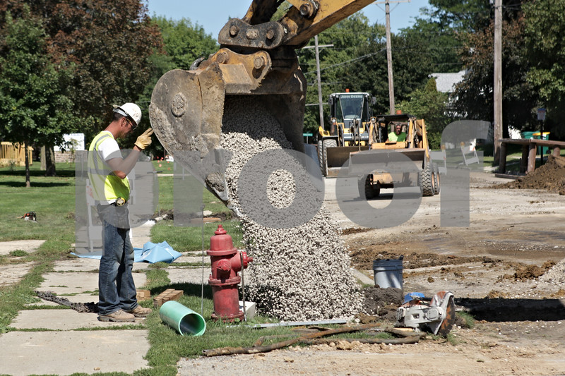 Rob Winner – rwinner@shawmedia.com<br /> <br /> Stones are poured around a pipe as new water main is installed on South First Street near Barb City Manor in DeKalb on Monday, Sept. 16, 2013. The completion date for the project is targeted for November 2. Residents from Taylor to Garden streets along South First Street are having their pipes replaced.