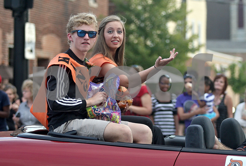 Monica Maschak - mmaschak@shawmedia.com<br /> Augi Jesmer and Kristin Johnson throw candy to spectators while riding along as part of the homecoming Court float during DeKalb's homecoming parade on Thursday, September 19, 2013.