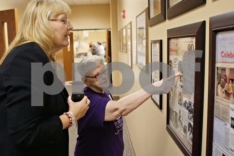 Rob Winner – rwinner@shawmedia.com<br /> <br /> Carla Raynor (left) and Diane Lockwood look over posters celebrating 50 years of Opportunity House during an open house event at their location in Sycamore on Thursday, Sept. 19, 2013.