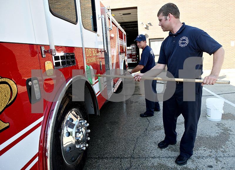 Monica Maschak - mmaschak@shawmedia.com<br /> Fire fighter paramedics Noah Millard (front) and Dave DeLille scrub the brand new fire engine at DeKalb Fire Station 1 on Friday, September 6, 2013.