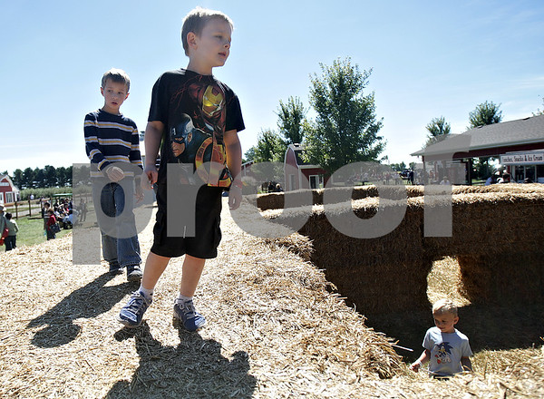 Monica Maschak - mmaschak@shawmedia.com<br /> Jacob Byers (right), 6, from Milwaukee, and Aaron Scott, 6, of Frankfort, run around the top of a straw maze at Jonamac Orchards on Saturday, September 14, 2013. The Orchards offer barnyard activities and apple picking through October.