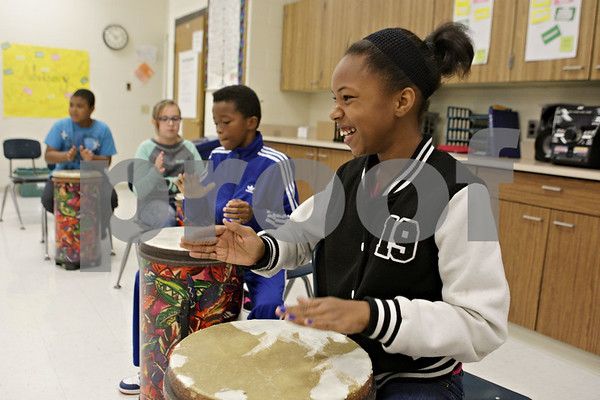 Rob Winner – rwinner@shawmedia.com<br /> <br /> Lyric Arielle Simmons, 11, beats on a drum during music class with her sixth grade classmates at Clinton Rosette Middle School in DeKalb on Tuesday, Sept. 17, 2013. All general music classes are set to be cut from middle schools in DeKalb after this academic school year.