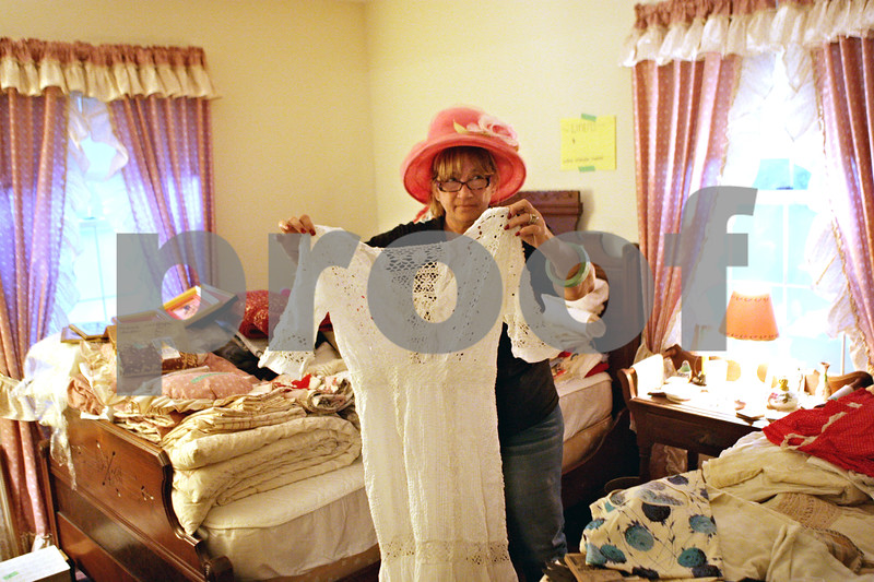 Rob Winner – rwinner@shawmedia.com<br /> <br /> Kathy Loos, owner of Kathy's Estate Sales, holds up a late nineteenth century wedding dress that belonged to the late Barbara (Groves) Wallin during an estate sale on Thursday morning in Sycamore.<br /> <br /> Thursday, Sept. 26, 2013
