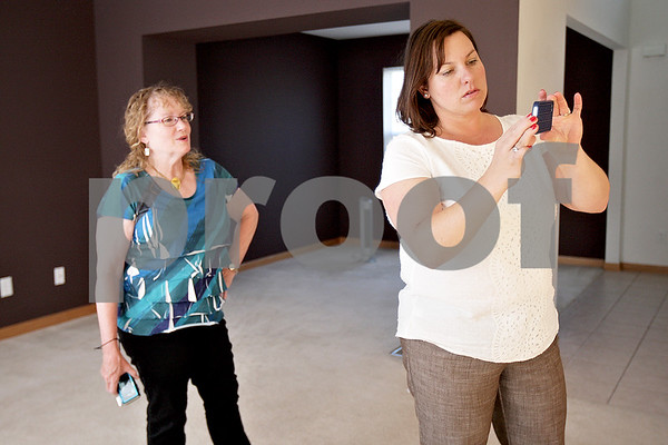 Monica Maschak - mmaschak@shawmedia.com<br /> Real Estate Investor Lindy Arnett (right) and Managing Broker Alison Rosenow take photos of a newly painted kitchen in a DeKalb home on Thursday, September 26, 2013. The photos will go into an updated brochure on the house.