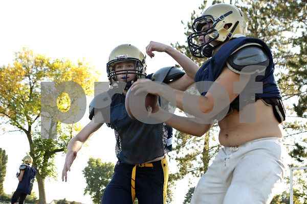 Rob Winner – rwinner@shawmedia.com<br /> <br /> Hiawatha quarterback Mike Mercado (right) fakes a handoff to running back Michael Speer during practice in Kirkland, Ill., Wednesday, Sept. 25, 2013.