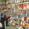 "Danielle Guerra - dguerra@shawmedia.com  Store manager Charles Fischer fixes comic books at Graham Crackers Comics on Paulina St. in DeKalb Monday afternoon. The store is preparing for it's 15th anniversary with different community events including a ""Clix for a Cause"" tournament on April 13 benefitting the Rochell Christian Food Pantry."