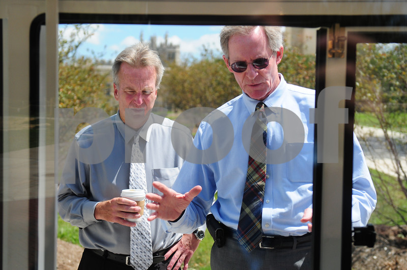 Bill Nicklas, vice president of operations and community relations at Northern Illinois University, discusses the new Huskie Pup Line with Chuck Walz, associate director of admission at NIU, on Thursday, August 14, 2014. The vehicle, an extended golf cart, is currently being tested by campus officials. The program will be up-and-running soon, Nicklas said. Lawerence Synett - lsynett@shawmedia.com
