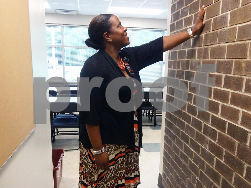 Tyler Elementary School Principal Andria Mitchell touches a wall in the teacher's lounge that used to be the main entrance to the school. The wall could have been covered or demolished, but was left standing to commemorate the school's original structure.