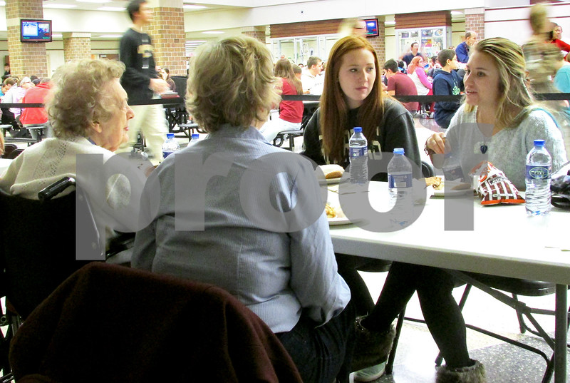 Katie Dahlstrom - kdahlstrom@shawmedia.com<br /> DeKalb High School seniors Maggie Fellabaum (left) and Holly Baker talk to Oak Crest resident Mary Smith (left) and her daughter Therese Laskowski at DeKalb High School on Wednesday during the third annual Seniors Lunching with Seniors event.