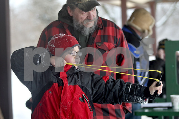 Monica Maschak - mmaschak@shawmedia.com<br /> Karl Peterson, 10, with Cub Scout Pack 118 of Sycamore, aims his sling shot with the guidance of Dan Thompson, a sportsman's club board member, at the annual Klondike Derby at the Sycamore Sportsman's Club on Saturday, February 1, 2014.