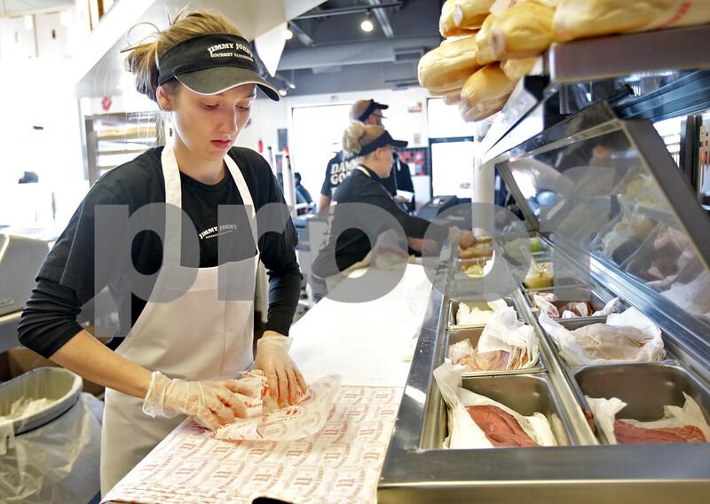 Monica Maschak - mmaschak@shawmedia.com<br /> Karlie Becker wraps a sandwich for a customer at Jimmy John's Gourmet Sandwiches in DeKalb on Monday, February 3, 2014.