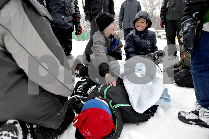 Monica Maschak - mmaschak@shawmedia.com<br /> DeKalb's Cub Scout Pack 131's Nathan Skeens, 9, lays on the ground and pretends to be injured as Donovan Dick, 9, and Houston Bai, 9, learn first aid techniques at the annual Klondike Derby at the Sycamore Sportsman's Club on Saturday, February 1, 2014.