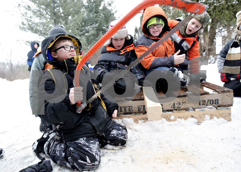 Monica Maschak - mmaschak@shawmedia.com<br /> Austin Machin, 9, of Cub Scout Pack 134 looks up proudly after sawing off a piece of wood at the annual Klondike Derby at the Sycamore Sportsman's Club on Saturday, February 1, 2014.