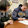Monica Maschak - mmaschak@shawmedia.com<br /> Lydia Short watches son Evan Short sign paperwork to play football at the University of Northern Colorado at Sycamore High School on Wednesday, February 5, 2014.