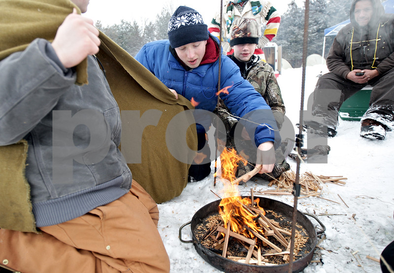 Monica Maschak - mmaschak@shawmedia.com<br /> Coy Thompson, 17, with Boy Scout Troop 26 of Kirkland, places more wood into the fire at the annual Klondike Derby at the Sycamore Sportsman's Club on Saturday, February 1, 2014.