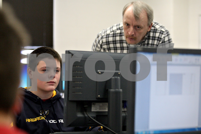 Monica Maschak - mmaschak@shawmedia.com<br /> Teacher Todd Johnson oversees eight grader Cole Dunbar's work on an in-class assignment in a computer lab at Hiawatha Middle School on Monday, February 10, 2014. Next year, students across Illinois will participate in PARCC testing via their school's computers.