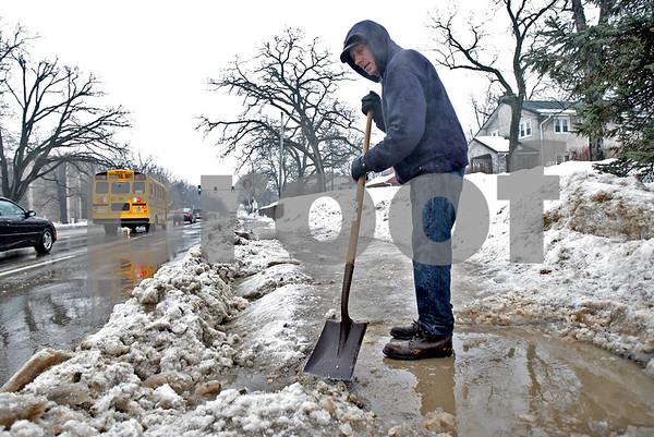 "Monica Maschak - mmaschak@shawmedia.com<br /> Dave Storm, of DeKalb, attempts to clear the thick ice covering the sidewalk bordering Lincoln Highway before the next drop in temperature on Thursday, February 20, 2014. ""I'm waiting for the rain to start working with me,"" Storm said."