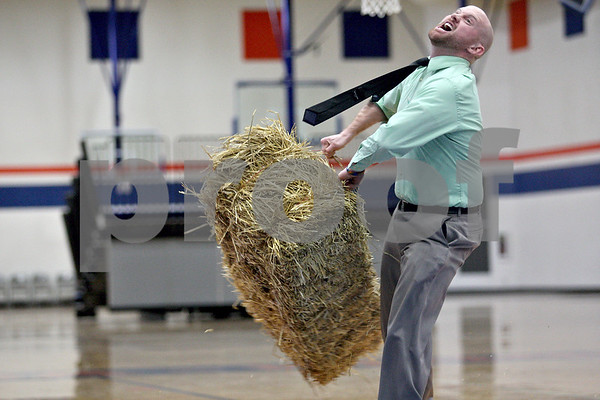 Monica Maschak - mmaschak@shawmedia.com<br /> Teacher Tom Rucker winds up with the hay bale before throwing it during the Ag Olympics at Genoa-Kingston High School on Tuesday, February 18, 2014. The students raised $175.93.