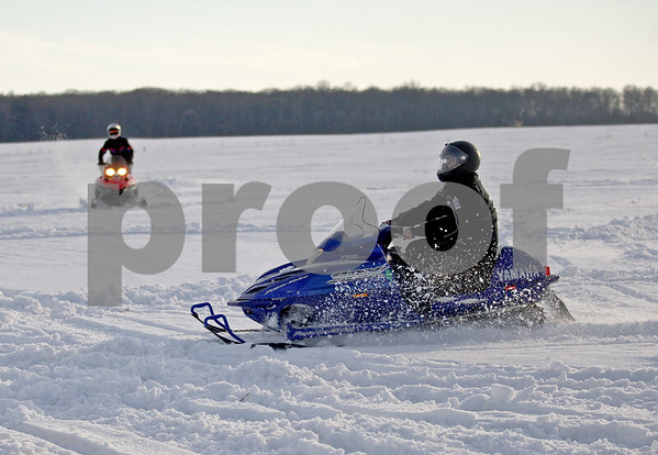 Monica Maschak - mmaschak@shawmedia.com<br /> Heath Strohacker (right), of Sycamore, and Zach Kein, 23, of Maple Park, ride their snowmobiles in an open field in Sycamore on Tuesday, February 18, 2014.
