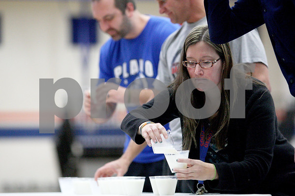 Monica Maschak - mmaschak@shawmedia.com<br /> Teacher Taryn Dennison cheats during a milk chugging competition by pouring her milk into her competitors' cups during the Ag Olympics at Genoa-Kingston High School on Tuesday, February 18, 2014. The students raised $175.93.