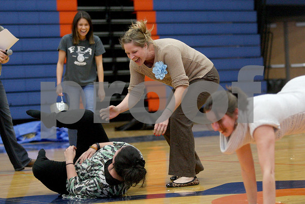 Monica Maschak - mmaschak@shawmedia.com<br /> Teachers Lisa Beynon (on the ground) and Tara Wilkens wipe out in a wheelbarrow race during the Ag Olympics at Genoa-Kingston High School on Tuesday, February 18, 2014. The students raised $175.93.