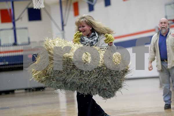 Monica Maschak - mmaschak@shawmedia.com<br /> Teacher Christi Volkening tosses a hay bale during the Ag Olympics at Genoa-Kingston High School on Tuesday, February 18, 2014. The students raised $175.93.
