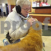 Andrea Azzo - aazzo@shawmedia.com<br /> DeKalb resident Carol Sturm pets Callan, a therapy dog, Friday at the This One's For the Girls women's health event at Kishwaukee Hospital.