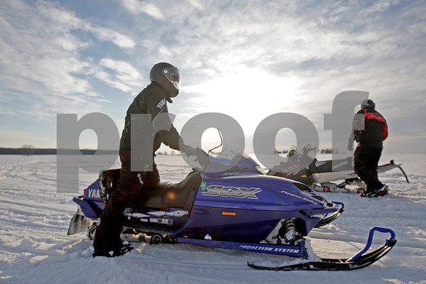 Monica Maschak - mmaschak@shawmedia.com<br /> Heath Strohacker (left) and Darrin Kein, both with the Genoa-Kingston Trailblazers, mount their snowmobiles in an open field in Sycamore on Tuesday, February 18, 2014.
